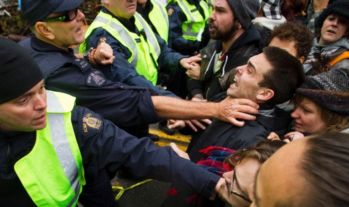 Protesters clash with Royal Canadian Mounted Police (RCMP) officers during a demonstration against the proposed Kinder Morgan pipeline on Burnaby Mountain in Burnaby, British Columbia November 20, 2014. REUTERS