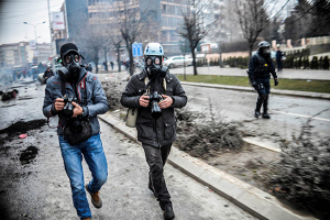 Photographer Visar Kryeziu, left, covers riots in Kosovo's capital Pristina, Tuesday, Jan. 27, 2015. Thousands of protesters clashed with police for hours in the city's streets, leaving a trail of destruction behind them. More than 80 people, including over 50 policemen, were injured, while 160 were detained. (Photo by Petrit Rrahmani)